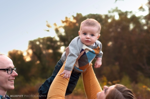 Kel Murphy Photography holiday mini sessions family of three mommy and daddy holding baby boy in the air