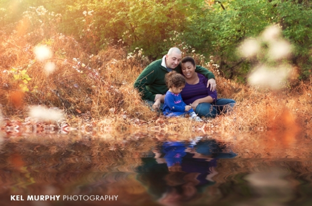 Family of three at lake reflection fall sunset golden hour photo shoot session by Kel Murphy Photography