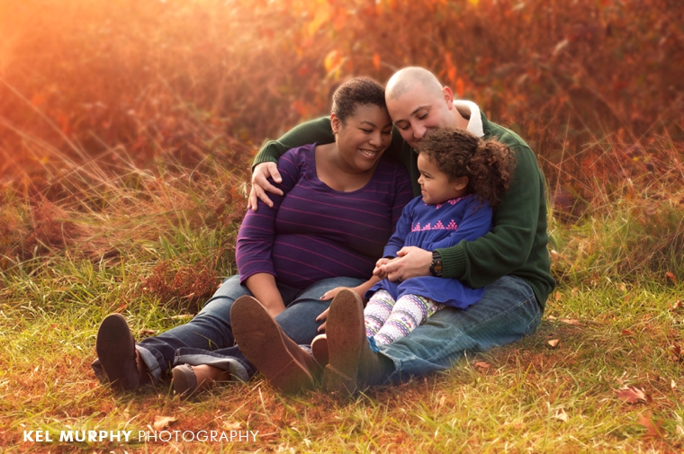 Family of three sitting outside fall sunset golden hour maternity pregnant photo shoot session by Kel Murphy Photography