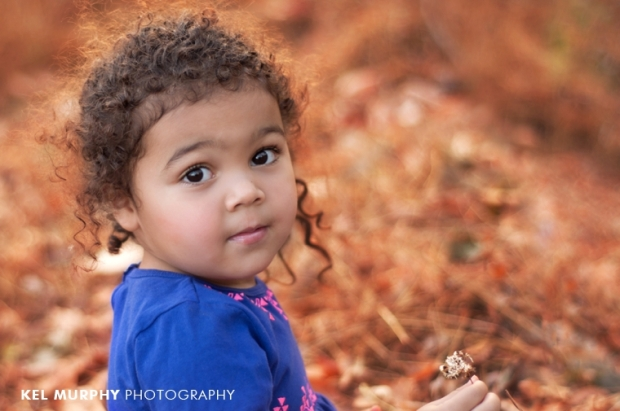 Little girl holding flower sitting outside in fall sunset three year old photo shoot session by Kel Murphy Photography