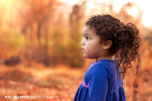 Little girl black curly hair silhouette outside in fall sunset three year old photo shoot session by Kel Murphy Photography