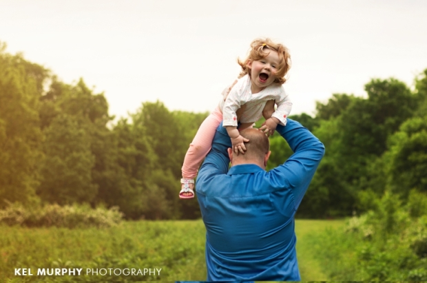 2 year old daughter being held above daddys head photo shoot session by Kel Murphy Photography