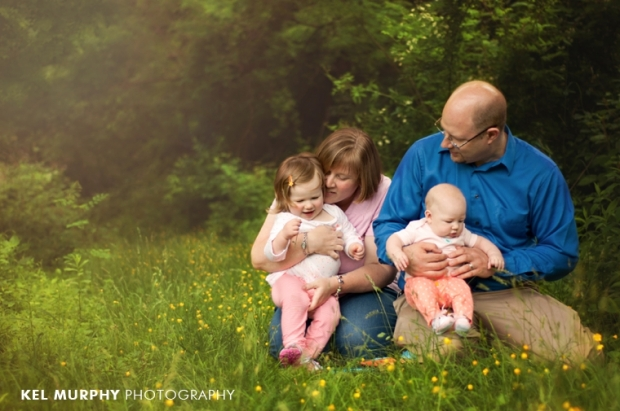 family of four cuddling in yellow buttercups photo shoot session by Kel Murphy Photography