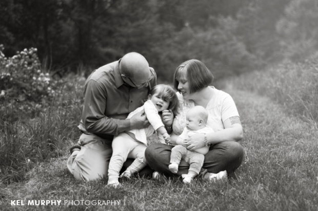 family of four outside in spring cuddling photo shoot bw session by Kel Murphy Photography