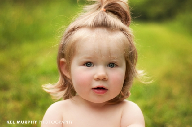 2 year old little girl half pony tail no shirt outside spring by Kel Murphy Photography