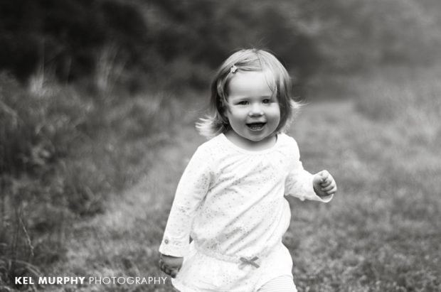 2 year old little girl running outside spring by Kel Murphy Photography