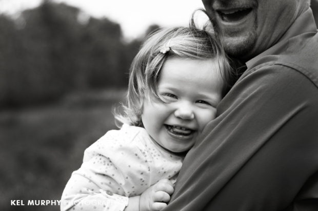 2 year old little girl laughing and squeezing daddy outside spring by Kel Murphy Photography
