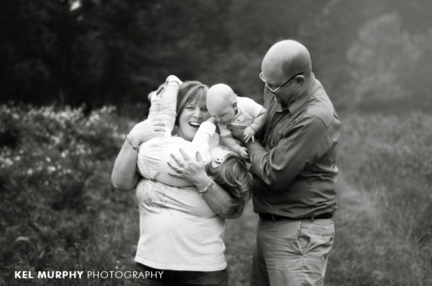 family of four real moment laughing outside in spring cuddling photo shoot bw session by Kel Murphy Photography